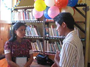 Librarian Raquel explains the library to a teacher