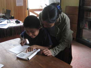 Librarian Raquel helps a student with his homework