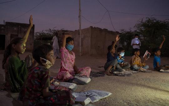 Children learn by the light of solar lanterns.
