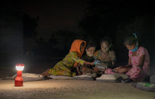 Girls read from a digital reader from  WorldReader