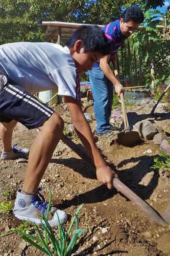 A student and teacher help clean the garden