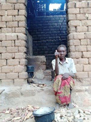 Woman showing Kitchen needing repair.