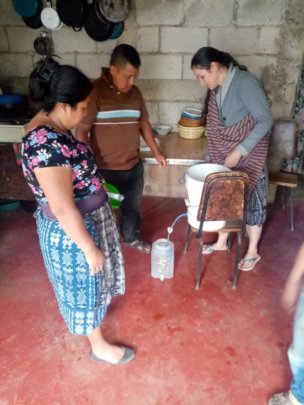 Beneficiary family receiving drinking water filter