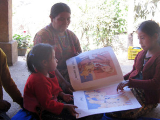 Hermalinda enjoying a picture book with her family