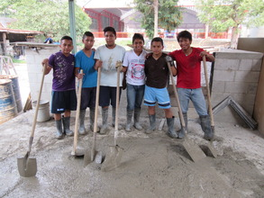 Members of the youth group help pour cement blocks