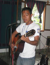Juan Carlos plays guitar at a talent show.