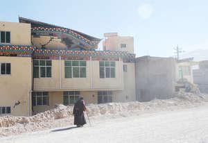 old woman walking down ruined street