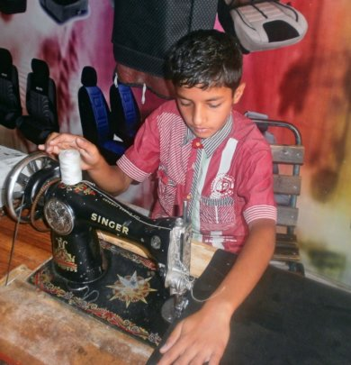 Ahsan sowing car seats at a car workshop