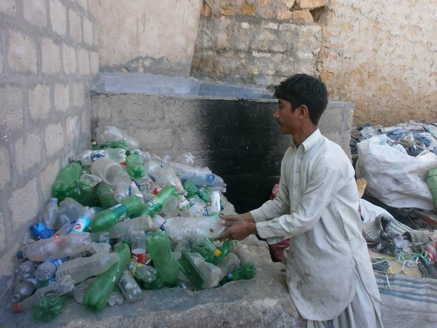 Azeem sorting plastic bottles at the scrap shop
