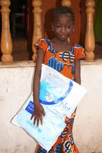 Beneficiary proudly holding her new mosquito net