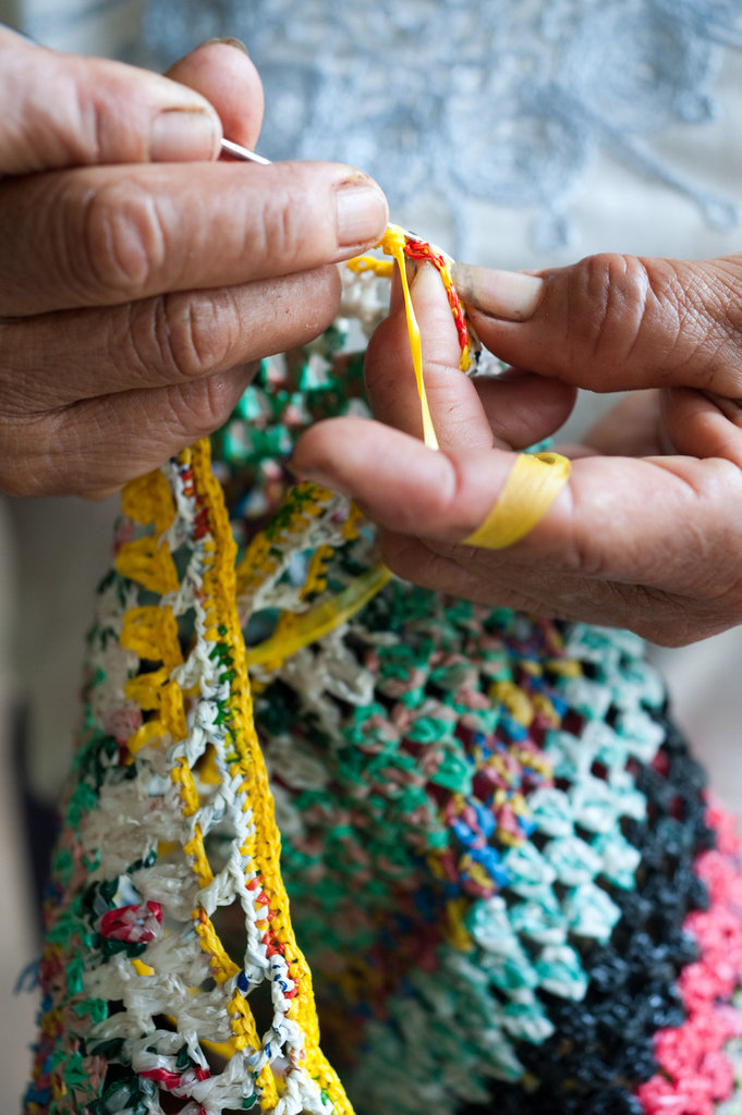 Weaving this bag made out of recycled plastic helps this woman from the community earn a sustainable income.