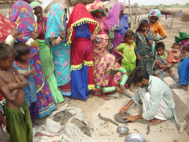 male helping women to learn FES cooking stove