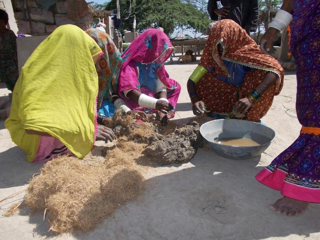 Women preparing mud for cooking stove