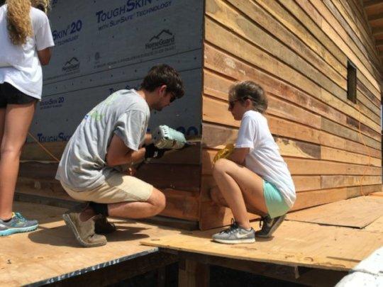 Volunteers work on housing construction
