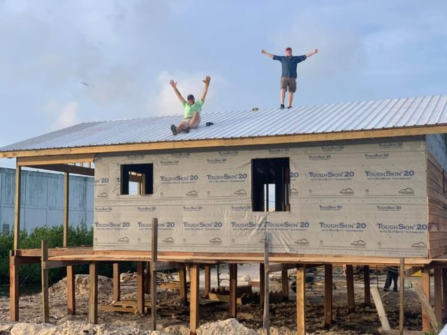 Volunteers celebrate after completing roof install