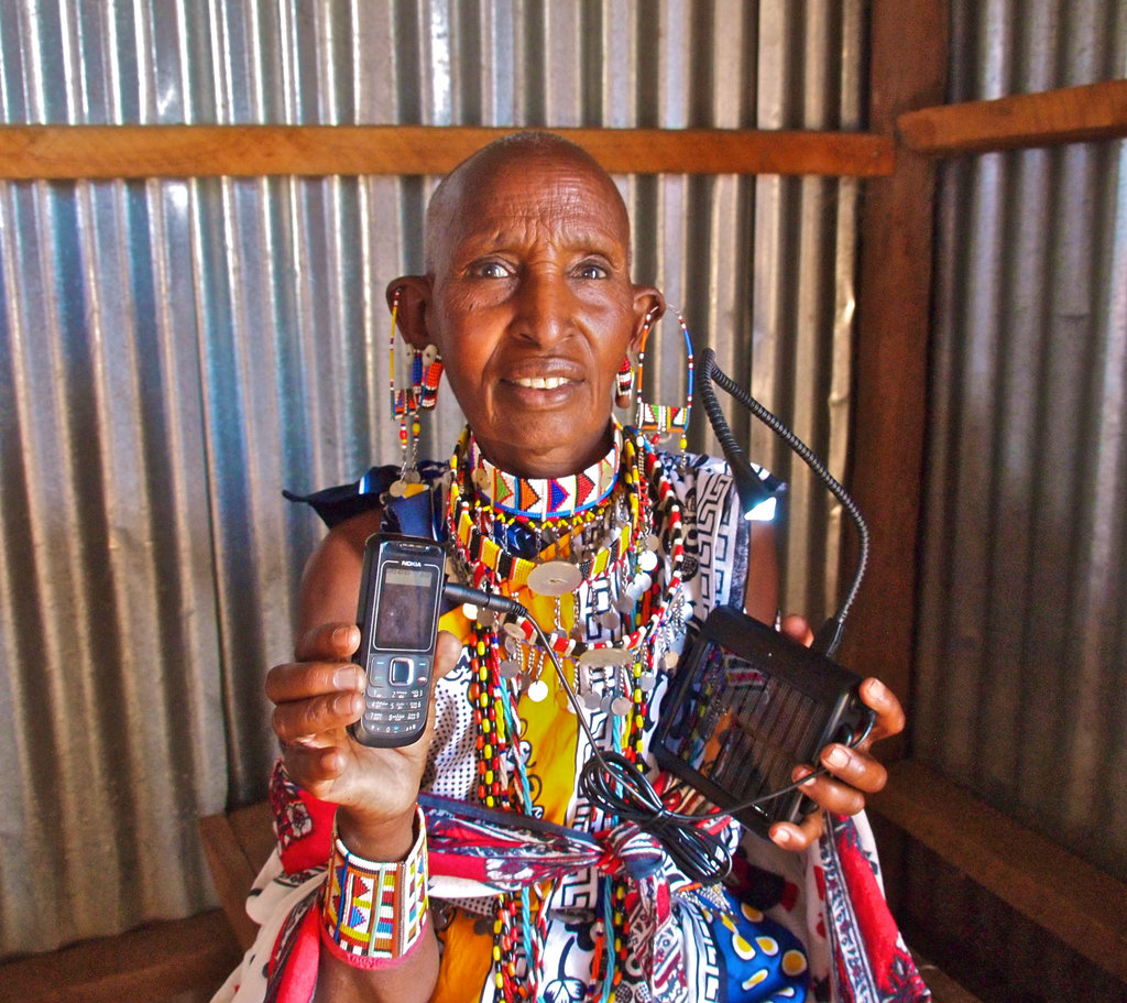 A woman & her phone  (A Maasai granny charging her cell phone with Lifeline Energy