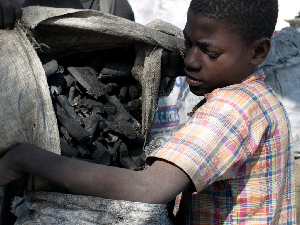 A young Haitian boy unloads bags of charcoal to be sold on the streets of Port-au-Prince. Haiti