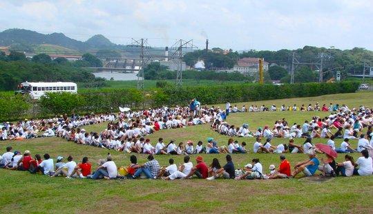 Hundreds of people gather along side Panama Canal