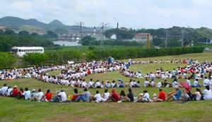 Hundreds of people gather along side Panama Canal