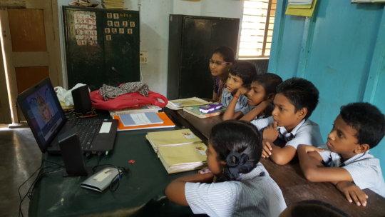 Schoolchildren and teacher watching AniBook story