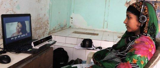 Woman watching SLS program in rural India