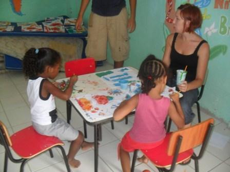 Children painting with a volunteer in Brazil