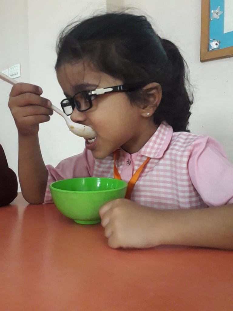 Enjoying her porridge with bananas and dates