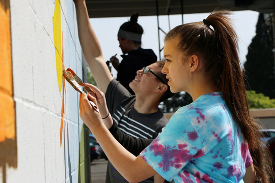 Youth take turns painting portions of a mural