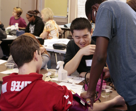 Joe guides youth through measuring blood pressure.