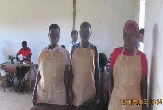 Tailoring students show off the aprons made