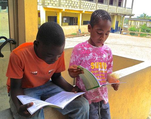 Kwesi and Derek enjoy reading their new textbooks!