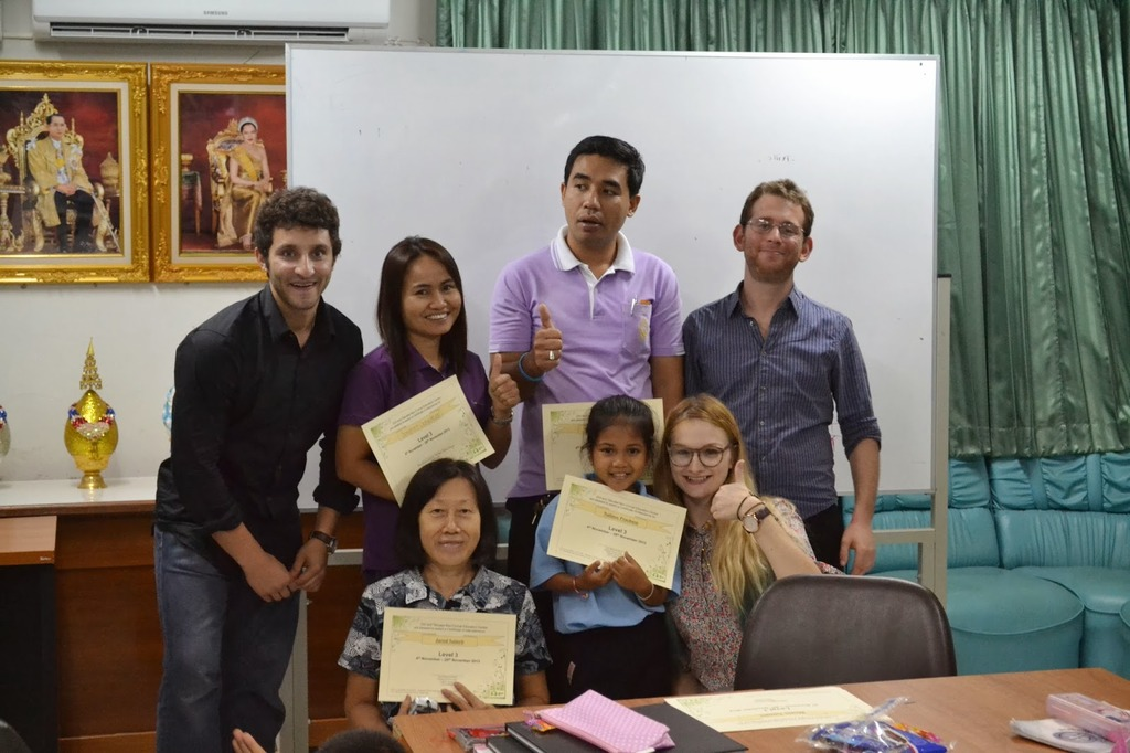 Three Thai students receiving their certificates