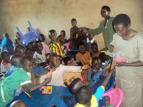 ECD teacher distributing the learning materials