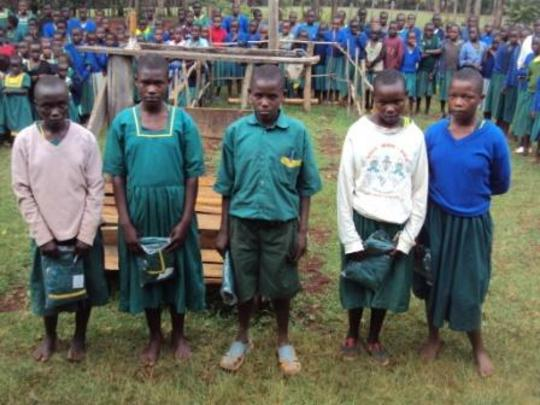 orphans in Nyambaria school receiving uniforms