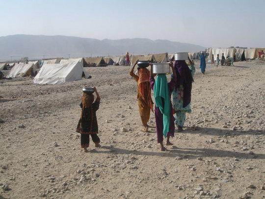 Women & children carrying water to tents...