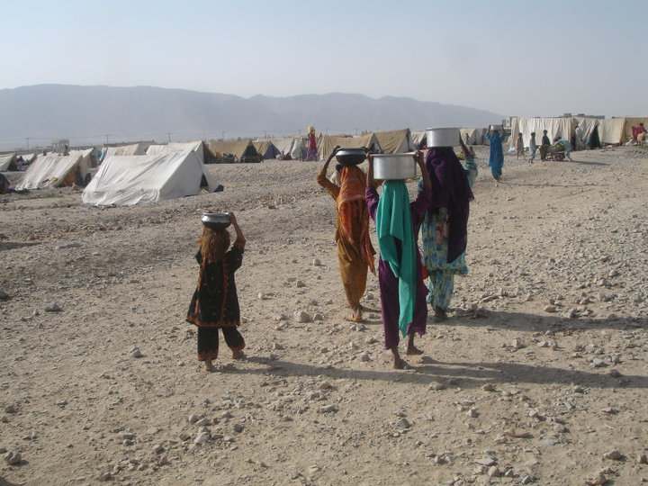 Women & children carrying water to tents...