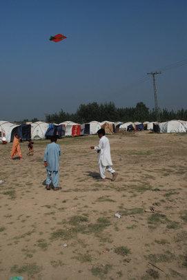 Children flying their kite near makeshift homes...