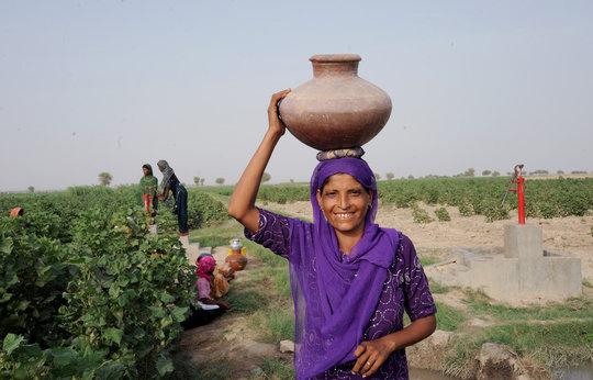 Taj Bibi carries water from the pump