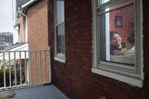 Isabel and her baby through their window