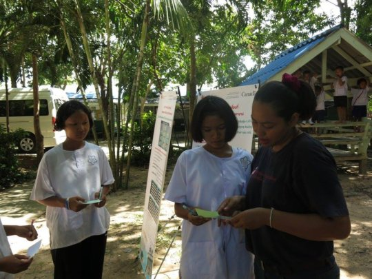 Nang explaining to two students