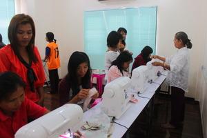 Girls focus on practicing sewing bag.