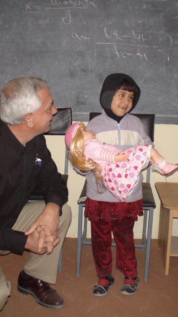 Little Safa smiling as she holds new doll
