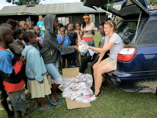 Volunteer providing shoes for children of Gioto