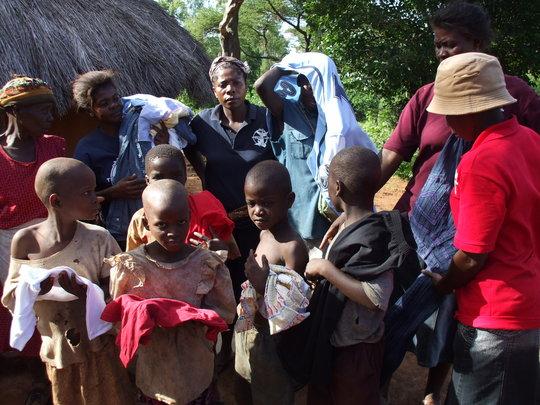 Caregivers distributing clorhing to poor kids