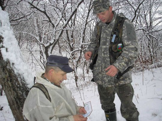 Detainee (in white camouflage cloak) and inspector
