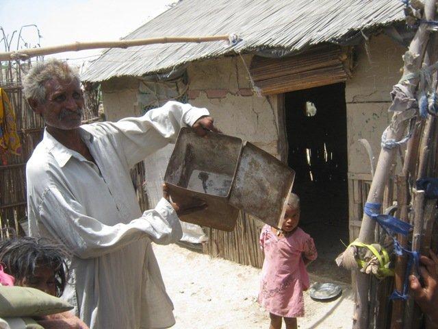 Mr. Juma showing empty box of flour / Atta