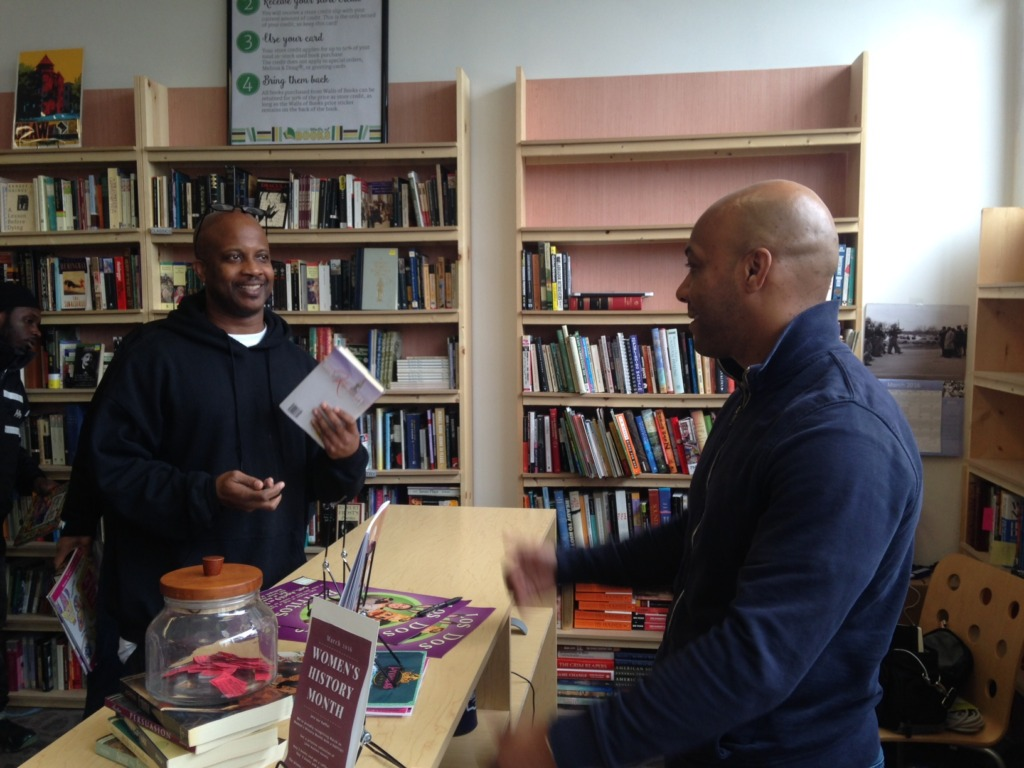 James (left) talks to Walls of Books owner Pablo