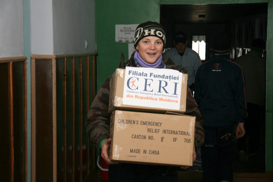 Children help carry boxes with boots