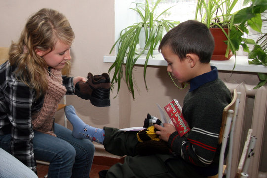 Volunteer student puts boots on orphan