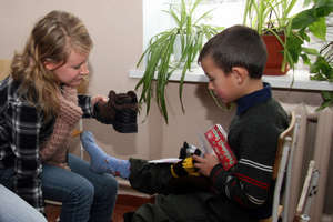 Volunteer student puts boots on orphan's feet